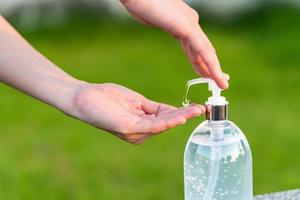 una persona che utilizza la pompa gel disinfettante per le mani all'esterno foto