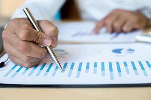 una persona finanziaria che traccia un grafico delle spese foto