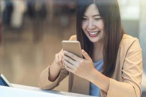 donna asiatica che per mezzo del telefono cellulare fuori del grande magazzino