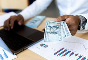 uomo d'affari che conta contanti a disposizione con il grafico finanziario allo scrittorio foto