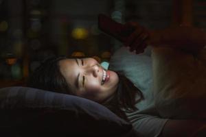 giovane donna asiatica che per mezzo del telefono mobile astuto per affrontare una persona amata prima di andare a letto foto