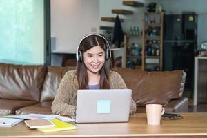 donna asiatica di affari che per mezzo del computer portatile di tecnologia a casa