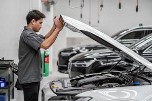 un meccanico guarda sotto il cofano dell'auto di un cliente nel centro servizi di manutenzione