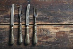 forchette e coltelli dall'alto su un tavolo di legno foto
