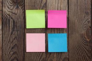 Nota di adesivi di carta multicolore su fondo di legno foto
