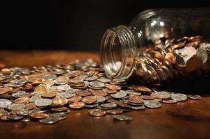 noi monete che si rovesciano dal grande barattolo di vetro foto