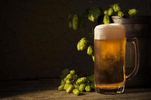 botte di birra con vetro sul tavolo di fondo in legno foto