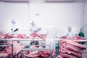 macellaio che taglia carne di maiale fresca foto