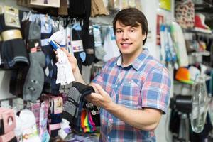 uomo che sceglie i calzini al negozio foto