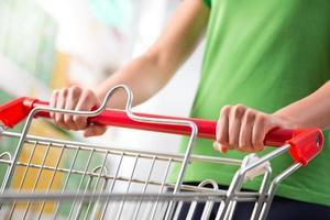 donna con carrello al supermercato foto