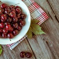 ciliegie mature fresche su una tavola di legno scura. foto