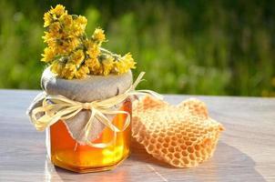 barattolo di miele pezzo di nido d'ape e fiori selvatici foto