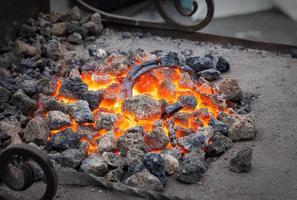 fabbro, ferro di cavallo in metallo viene riscaldato nella fucina sui carboni foto
