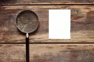 lente d'ingrandimento e un foglio di carta su un fondo di legno foto
