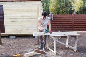 uomo tagliato trave di legno con sega circolare foto