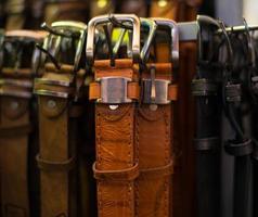 collezione di cinture in pelle nel negozio. foto