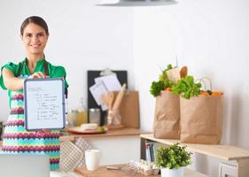 donna in cucina a casa, in piedi vicino alla scrivania con foto
