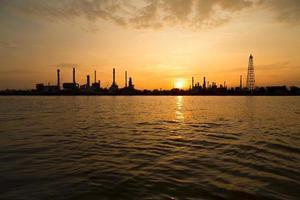 Siluetta della pianta di industria della raffineria di petrolio di mattina foto