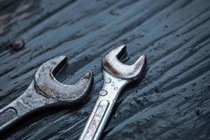 strumento chiave con goccia di rugiada in cima al tavolo di legno foto