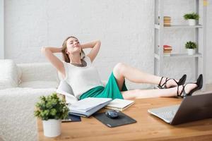 imprenditrice riposo gambe rilassanti sul tavolo le mani dietro di lei foto