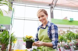 donna felice che tiene i fiori in serra