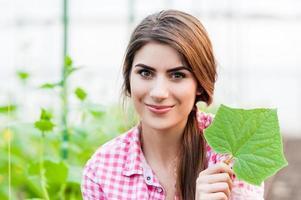 donna che fa il giardinaggio tenendo una foglia di cetriolo.