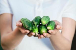 giovane donna con cetrioli in mano