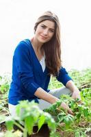 bella giovane donna che fa il giardinaggio e che sorride alla macchina fotografica.