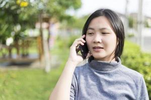 donna che parla sullo smartphone al parco giochi foto