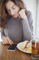 donna con telefono e sandwich foto