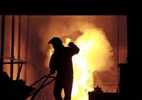 uomo che lavora nel ferro fuso che spruzza - immagine di riserva