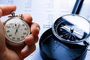mano che tiene il cronometro sui numeri di bilancio foto