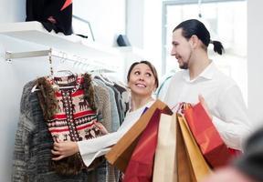 coppia scegliendo giacca al negozio di abbigliamento foto