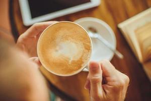le mani degli uomini tengono il caffè e il libro sul tavolo foto