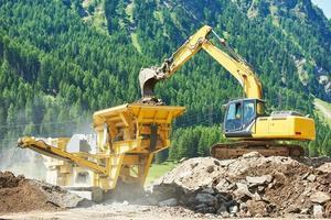escavatore e macchina frantoio per pietre foto