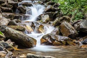 la cascata cade sulle rocce di montagna foto