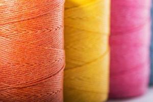 rocchetti di filo in giallo, arancione e rosa foto