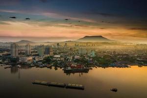 paesaggio urbano vicino al fiume in alba con sfondo di montagna foto