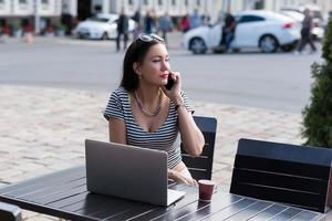 donna di affari che parla sul telefono cellulare durante il lavoro sul net-book portatile foto