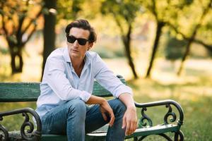 uomo attraente seduto da solo in panchina con il cellulare foto