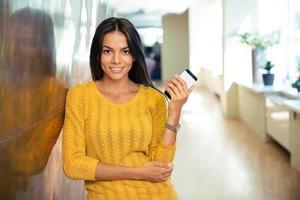 smartphone felice della tenuta della donna di affari casuale foto