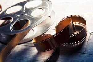 primo piano di una bobina di film con pellicola marrone su una superficie di legno foto