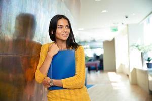 imprenditrice in piedi con la cartella in corridoio foto