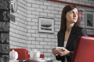 giovane donna con una tazza di tè nella caffetteria foto