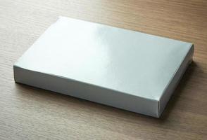 scatola di carta grigia in bianco su fondo di legno scuro foto