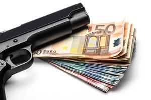 mazzo di banconote in euro con una pistola foto