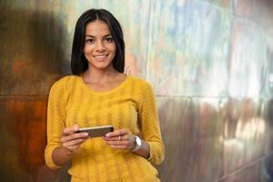 donna di affari sorridente che per mezzo dello smartphone foto