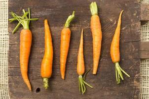 carote completamente naturali allineate su tavola di legno