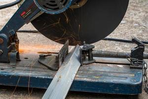 taglio di un triangolo in metallo e acciaio con troncatrice composta foto