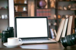 pila di vecchi libri e laptop sul tavolo di legno foto